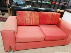 Description An indian red two seater couch (160 x 80 x 80 cm)  This bid will be used as your proxy bid on our live auction - Online bidders will be notified by 6 Pm by Auction day. AP Score 10/10.. This is a live and online auction.