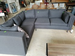 Description Stunning modern grey material corner lounge suite with steel legs & scatter cushions (240 x 270 x 110 cm)  This bid will be used as your proxy bid on our live auction - Online bidders will be notified by 6 Pm by Auction day. AP Score 10/10. This is a live and online auction.