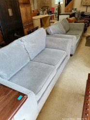 Description A modern comfy grey material lounge suite 2 x two seaters.  (200 x 100 x 100 cm).  Auctioned as a a set.    This bid will be used as your proxy bid on our live auction - Online bidders will be notified by 6 Pm by Auction day. AP Score 10/10.. This is a live and online auction.
